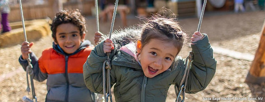 Two young children laugh while on the swings in the outdoor play area of the Nada Sage Waldorf School in Reno, Nevada.