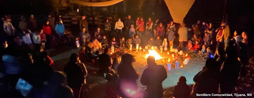 Community members gather around a small fire surrounded by lanterns, at Semillero Comunalidad in Tijuana, Mexico.