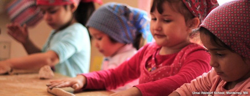 Four kindergarteners roll out bread dough with their hands at Umai Waldorf School in Monterrey, Mexico.