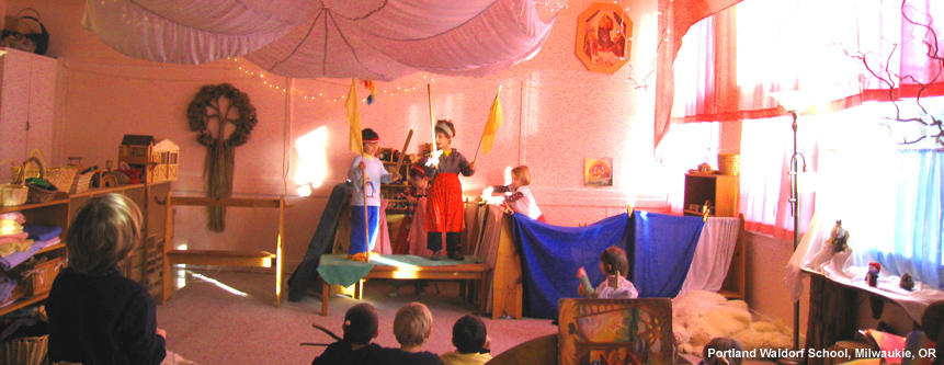 Two grade school children at Portland Waldorf School in Milwaukie, Oregon put on a skit for six young children.