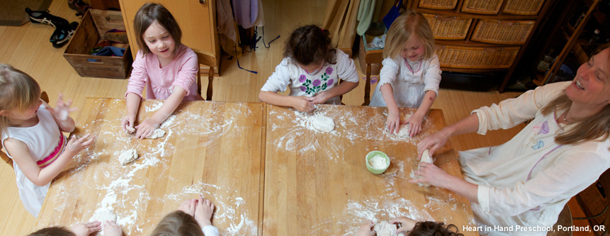 At Heart in Hand Preschool, seven children sit kneading bread dough with their teacher.