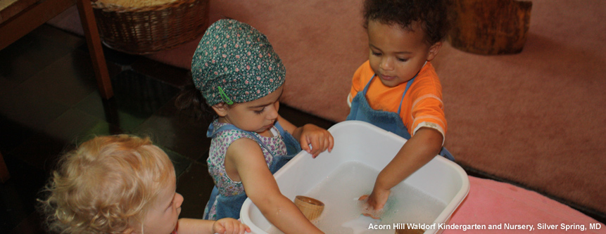 Three children wash cups in a tub of warm water at Acorn Hill Waldorf Kindergarten and Nursery in Silver Spring, Maryland.
