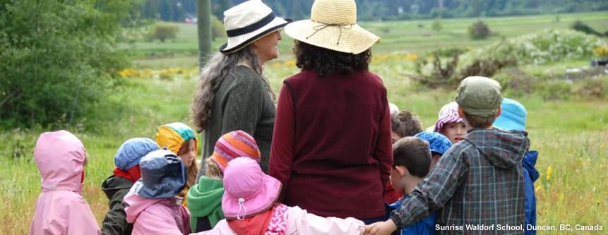 An early childhood class dressed for rain, walk in a meadow with their teachers at Sunrise Waldorf School in Duncan, British Columbia, Canada.